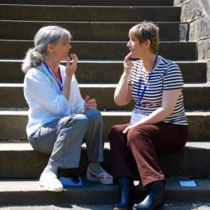 Two women tapping in sunshine